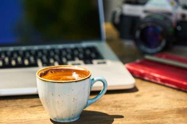 a cup of coffee and a camera on a wooden table in the workplace